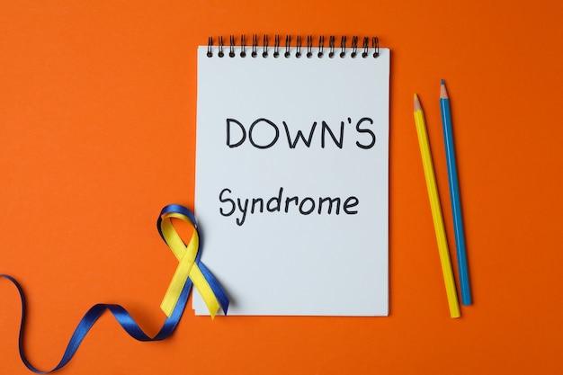 Tekst het syndroom van down, bewustzijnslinten en potloden op oranje