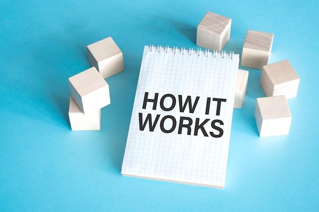 Tekst hoe het werkt op wit notitieblok met kubusblok