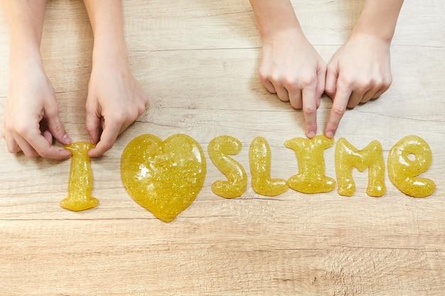 Tekst ik hou van glimlach op tafel. childs speelt met slijm. zelfgemaakt populair speelgoedslijm. creatieve kinderen