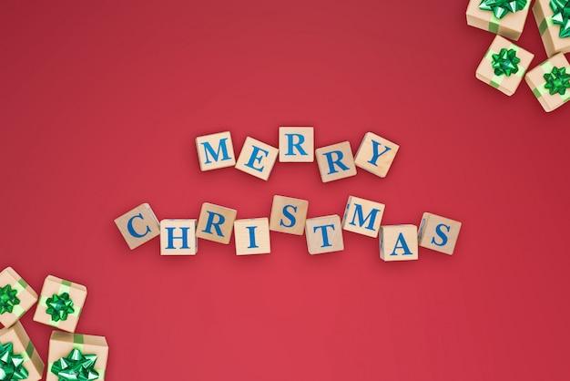 Tekst inscriptie merry christmas aangelegd van houten kubussen op rode achtergrond