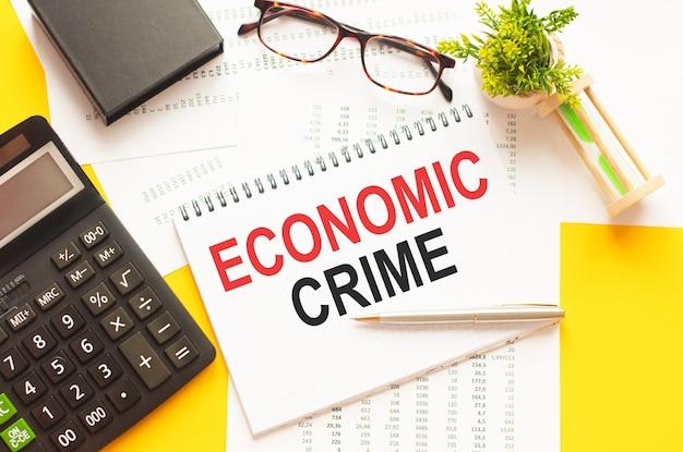 Tekst intoetsen met economische criminaliteit. tekst schrijven economic crime op wit papier kaart, rode en zwarte letters, gele muur. bedrijfsconcept.