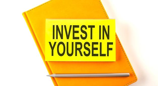 Tekst invest in jezelf op sticker op het gele notitieboekje