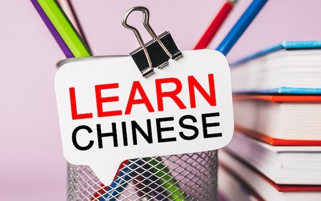 Tekst leer chinees op een witte sticker met de achtergrond van kantoorbenodigdheden. plat op concept voor zaken, financiën en ontwikkeling