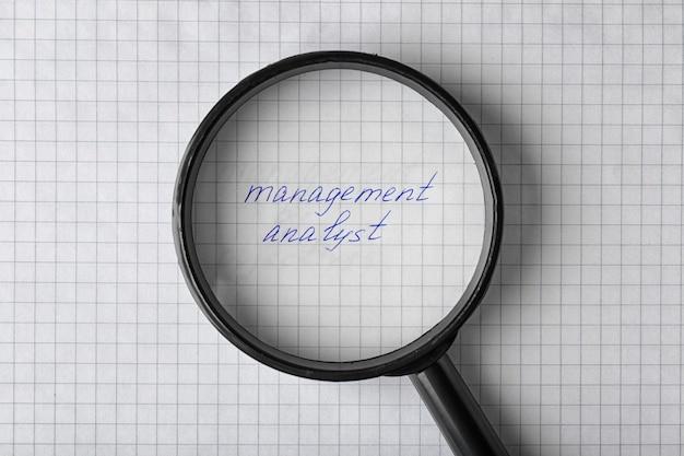 Tekst management analyst onder vergrootglas op papier bladachtergrond