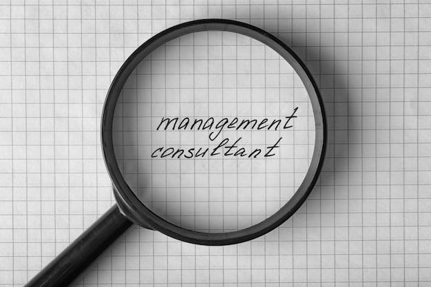 Tekst management consultant onder vergrootglas op papier bladachtergrond