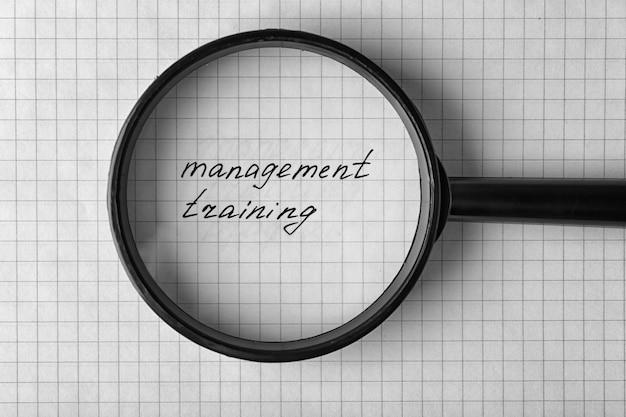 Tekst management training onder vergrootglas op papier bladachtergrond