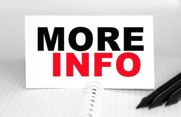 Tekst meer info op papieren kaart, potloden op tafel - concept voor bedrijven, banken, financiën en investeringen.