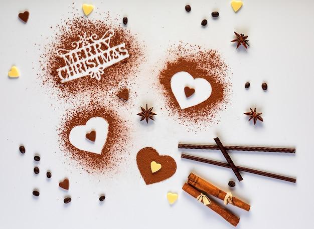 Tekst met cristmas-concept en drie hartvormen van cacaopoeder, muntstokken en kaneelstokjes