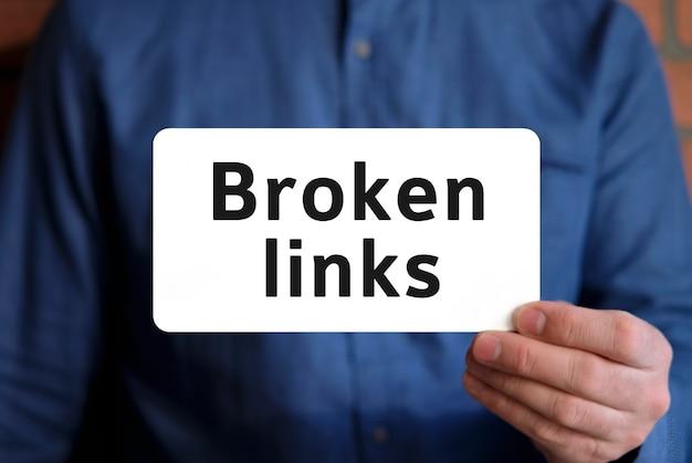 Tekst met gebroken links op een wit bord in de hand van een man in een blauw shirt