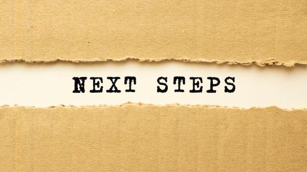 Tekst next steps verschijnt achter gescheurd bruin papier