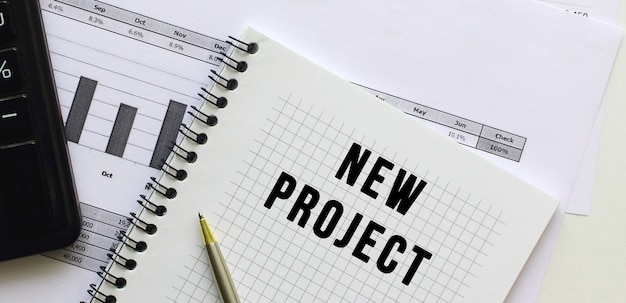 Tekst nieuw project op de pagina van een notitieblok liggend op financiële grafieken op het bureau.