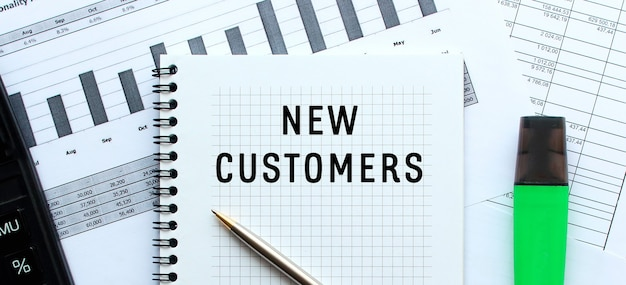 Tekst nieuwe klanten op de pagina van een notitieblok dat op financiële grafieken op het bureau ligt. bij de rekenmachine. bedrijfsconcept.