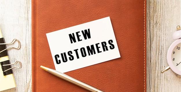 Tekst nieuwe klanten op witte kaart liggend op kladblok op bureau.