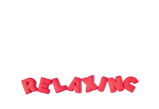 Tekst ontspannend gespeld met rode alfabetvormige koekjes op witte achtergrond
