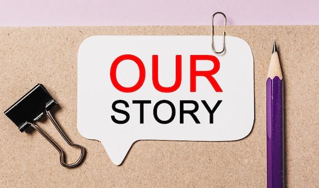 Tekst our story op een witte sticker met kantoorbenodigdheden