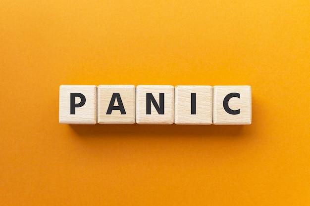 Tekst paniek op houten kubussen op fel oranje oker achtergrond oncontroleerbare angst of angst mental