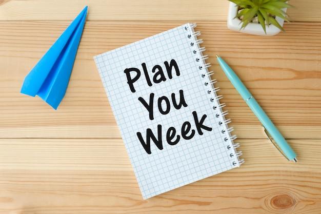 Tekst plan uw week op kalenderplanner om u aan een belangrijke afspraak te herinneren met een pen op houten achtergrond