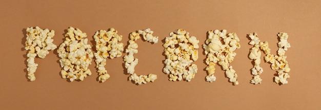 Tekst popcorn op bruine ruimte, bovenaanzicht. eten voor bioscoop