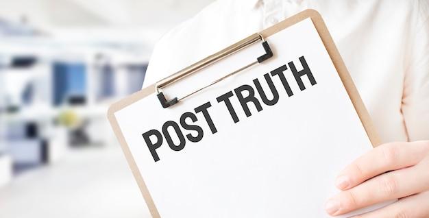 Tekst post waarheid op wit papier bord in zakenman handen in kantoor. bedrijfsconcept