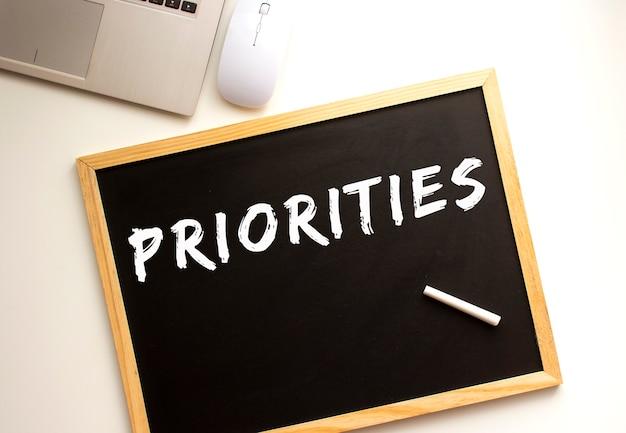 Tekst prioriteiten geschreven met krijt op een leisteen bord