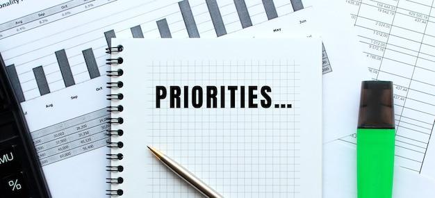 Tekst priorities op de pagina van een blocnote die op financiële grafieken op het bureau ligt