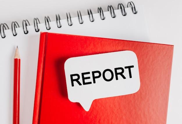 Tekst rapport een witte sticker op rode blocnote met kantoorbenodigdheden achtergrond. plat op concept voor zaken, financiën en ontwikkeling