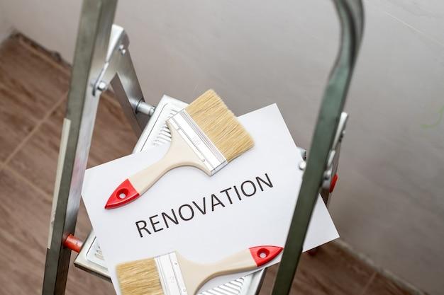 Tekst renovatie, zwarte letters op wit papier. huisverbetering, vuile verfladder, roller, kwast en bakje. reparatiekamer. trapladder en verschillende gereedschappen in de kamer. interieur renovatie