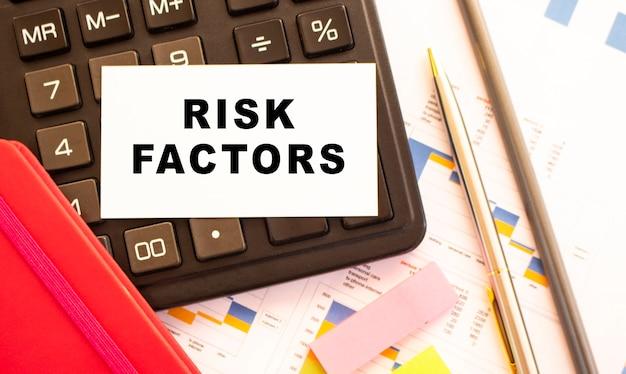 Tekst risicofactoren op witte kaart met metalen pen. bedrijfs- en financieel concept
