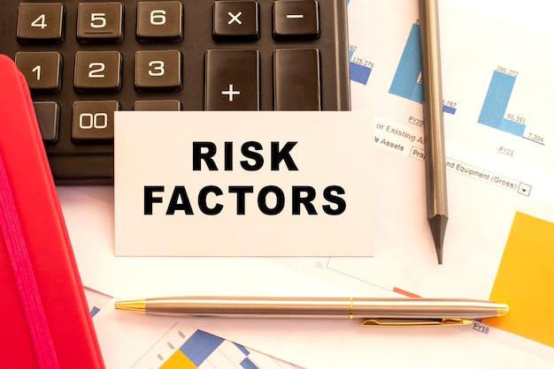 Tekst risicofactoren op witte kaart met metalen pen, rekenmachine en financiële grafieken