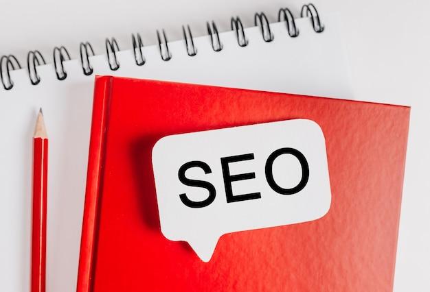 Tekst seo een witte sticker op rode blocnote met kantoorbenodigdheden achtergrond. plat op concept voor zaken, financiën en ontwikkeling