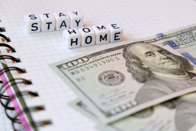 Tekst stay home, word gemaakt van kubieke letters en amerikaanse geld dollars op een witboek voorbeeldenboek