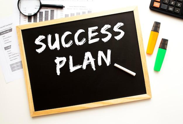Tekst succesplan geschreven met krijt op een leisteen bord. bureau met kantoorbenodigdheden. bedrijfsconcept.