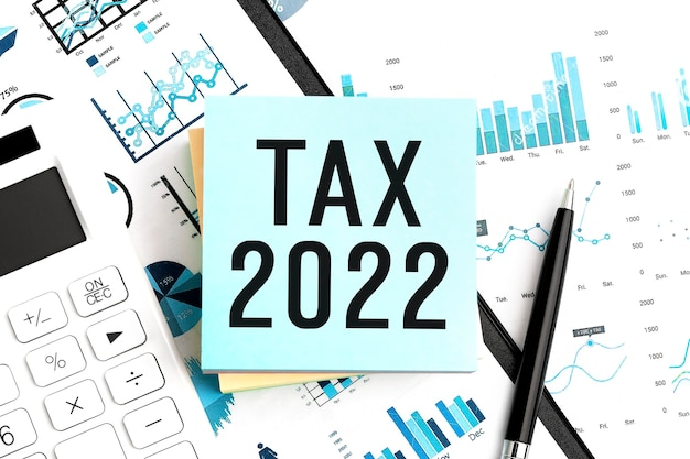 Tekst tax 2022 op sticker. pen en rekenmachine op klembord met grafieken, documenten en grafieken. bedrijfsconcept. plat leggen.