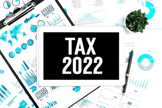 Tekst tax 2022 op tablet. klembord, pen, plant, grafiek, document en grafiek achtergrond. bedrijfsconcept. plat leggen.