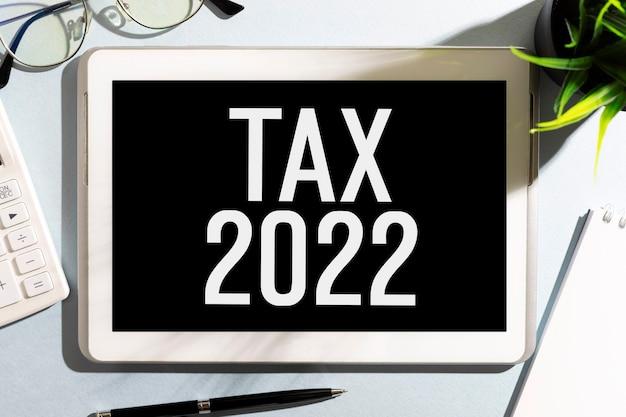 Tekst tax 2022 op tablet, rekenmachine, glesses, notitieblok. boekhoudkundig concept. plat leggen.