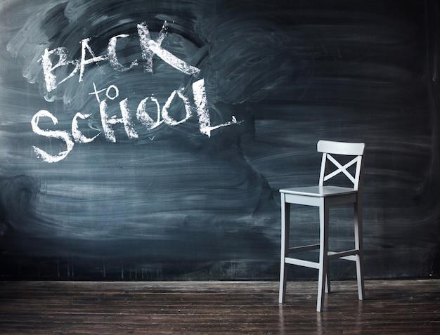 Tekst terug naar school op een zwart bord. houten stoel tegen een schoolbank voor de brief