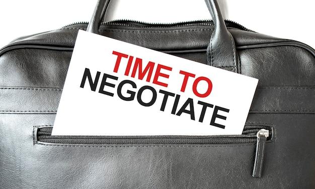 Tekst tijd om te onderhandelen door op een wit vel papier in de zwarte zakelijke tas te schrijven. bedrijfsconcept