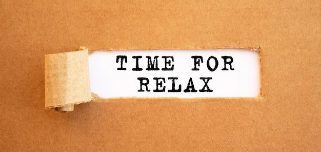 Tekst time for relax verschijnt achter gescheurd bruin papier.