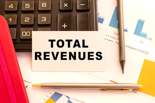 Tekst totale inkomsten op witte kaart met metalen pen, rekenmachine en financiële grafieken