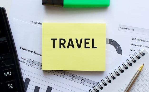 Tekst travel op de pagina van een notitieblok dat op financiële grafieken op het bureau ligt