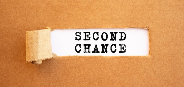 Tekst tweede kans verschijnt achter gescheurd bruin papier. voor uw ontwerp, concept.