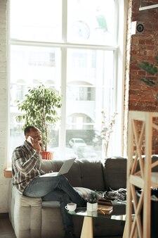 Tekst typen en praten over de telefoon. man, freelancer tijdens het werk in het kantoor aan huis tijdens quarantaine. jonge zakenman thuis, zelf geïsoleerd. gadgets gebruiken. werken op afstand, preventie van verspreiding van coronavirus.