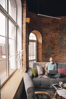 Tekst typen. jonge man die thuis yoga doet terwijl hij in quarantaine zit en freelance online werkt
