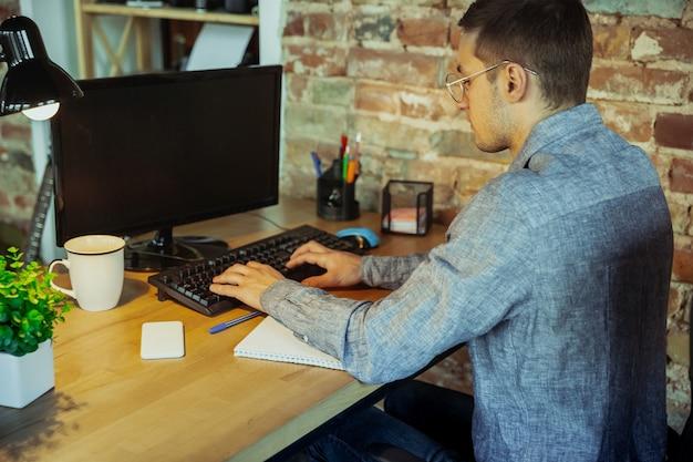 Tekst typen. man aan het werk vanuit huis tijdens coronavirus of covid-19 quarantaine, extern kantoorconcept. jonge zakenman, manager die taken doet met smartphone, computer, heeft online conferentie, vergadering.