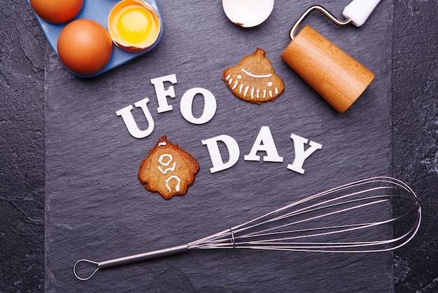 Tekst ufo-dag en koekjes in de vorm van een vliegende schotel en een alien