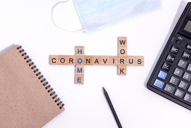 Tekst uit houten brieven coronavirus werken vanuit huis. kantoorartikelen, een rekenmachine, papier kladblok voor notities, een potlood en een beschermend medisch masker op het bureaublad.