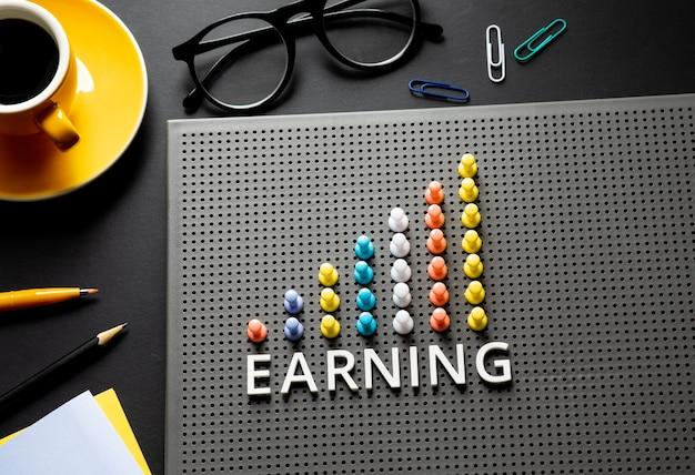 Tekst verdienen met pin-garph-grafiek op bedrijfstafel. visie op succes en strategisch plan.