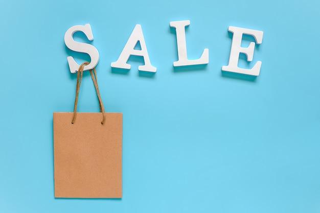 Tekst verkoop van witte volume letters en blanco papieren boodschappentas op blauw.