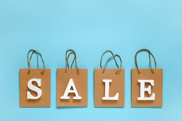 Tekst verkoop van witte volume letters en lege boodschappentassen op blauwe achtergrond.