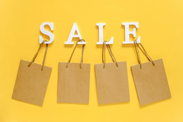 Tekst verkoop van witte volumebrieven en lege boodschappentassen. concept korting.